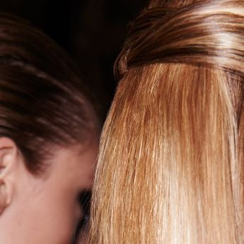 Close up of the side of two model's heads, with their hair in the same style, with the side sections wraped around the back of the head in a loose braid