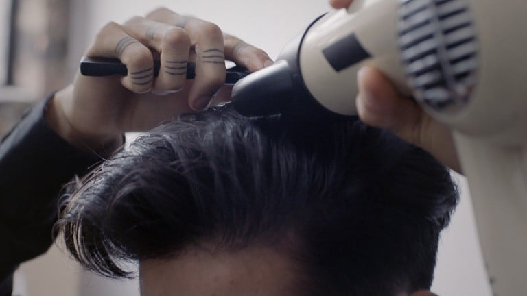 A dark-haired guy, blowdrying his hair.