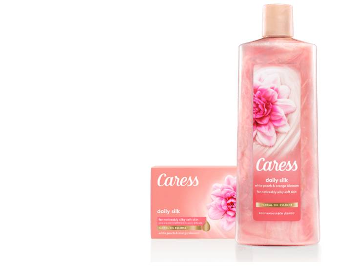 Caress Daily Silk 18z Body Wash y Beauty Bar (caja de cartón + barra) sobre un fondo morado.
