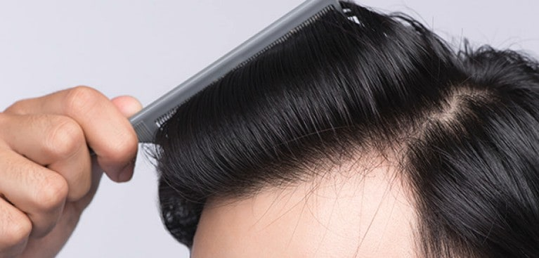 Closeup of short sleek black hair being combed