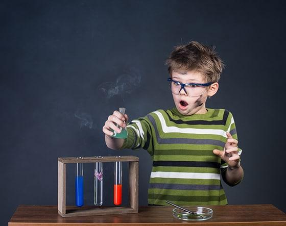 Niño con gafas azules hace experimentos quimicos
