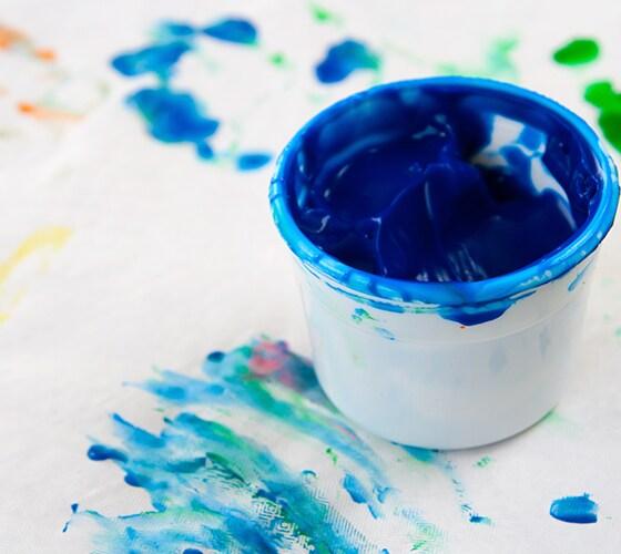 Tarro blanco lleno de pintura azul sobre superficie pintada