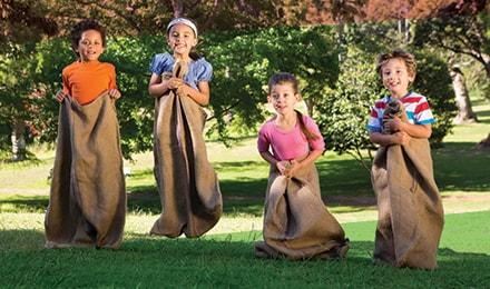 Cuatro niños saltan dentro de sacos en un parque