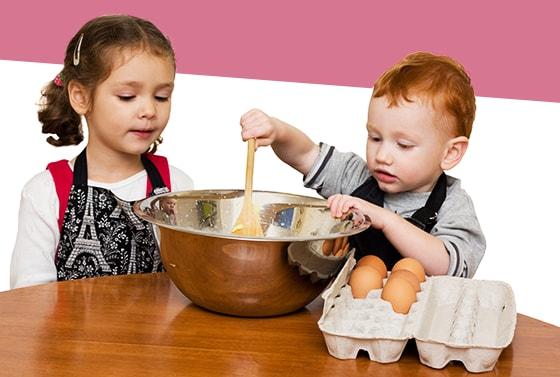 Niña y un niño baten una mezcla en un tazon metalico