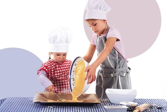 Dos niños con gorros blancos pasan una mezcla a un recipiente rctangular