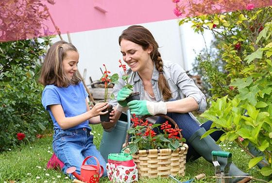 Madre y su hija en un jardín lleno de plantas