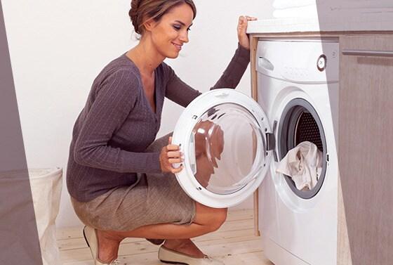 Mujer en falda abre la lavadora para sacar ropa