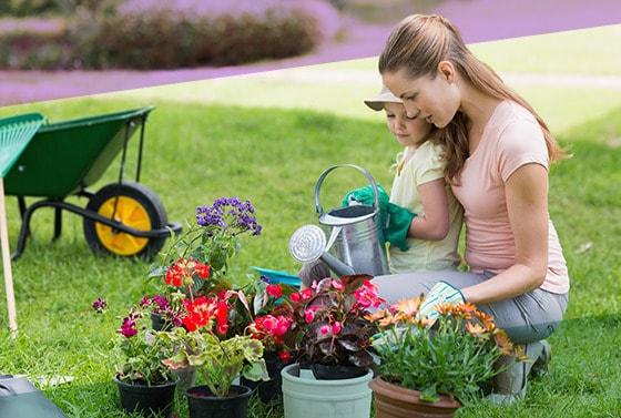 Madre y su hija riegan varias plantas en materas