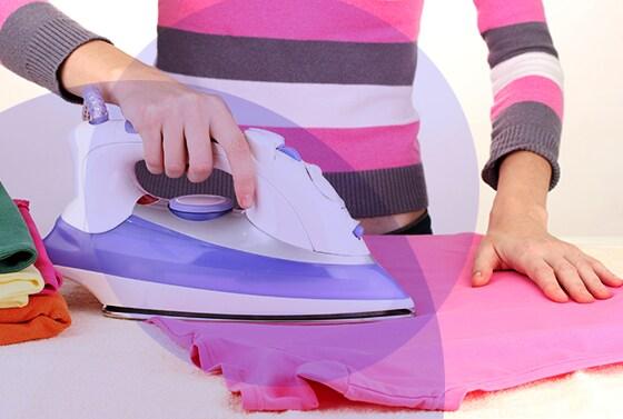 Mujer plancha camisa de color rosado
