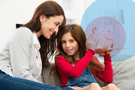 Madre mira a su hija quien tiene una alcancia en sus manos