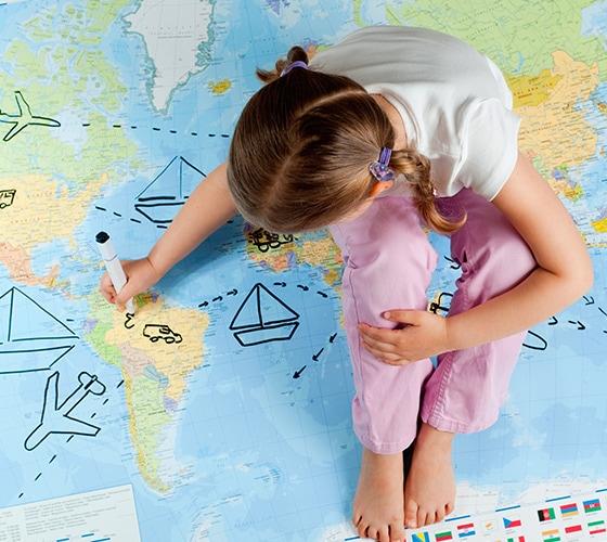 Niña sentada dibujando sobre mapamundi