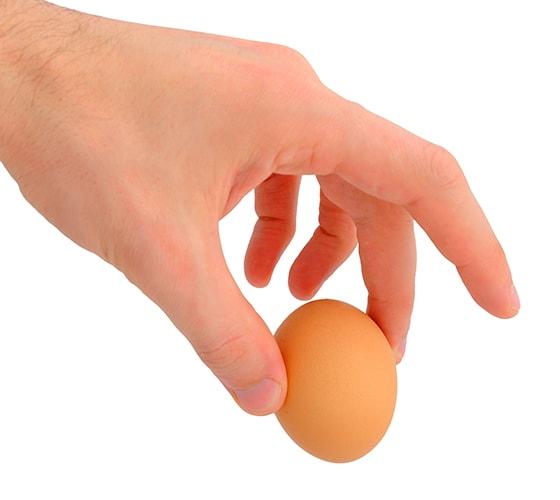 Mano sostiene un huevo en el aire