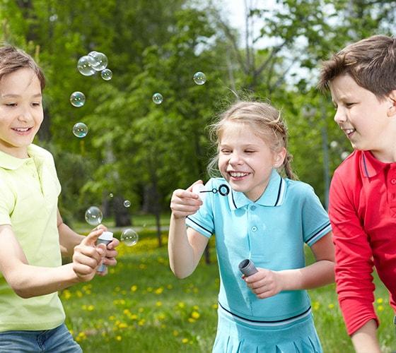 Niños jugando a hacer burbujas de jabon en un parque