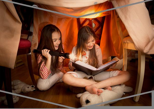 Dos niñas leen un libro grande utilizando una linterna