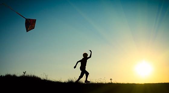 Niño vuela una cometa solo mientras el sol cae