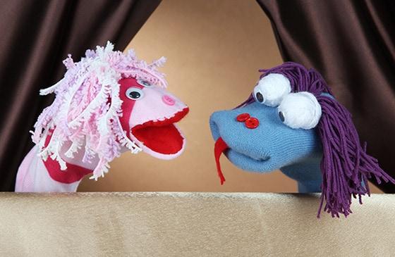 Marioneta azul y rosada juntas en bajo un telon>