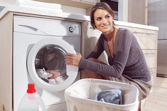 Mujer sonriente saca la ropa de la lavadora