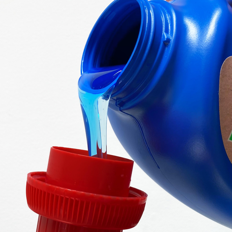Aplicando detergente liquido de fab con una tapa azul