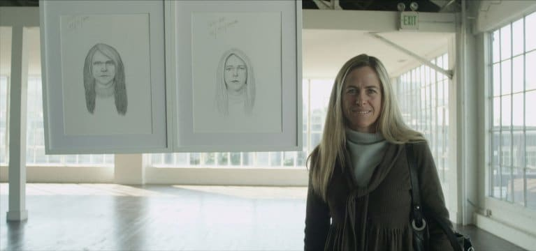 Blonde woman standing beside two potrait sketches