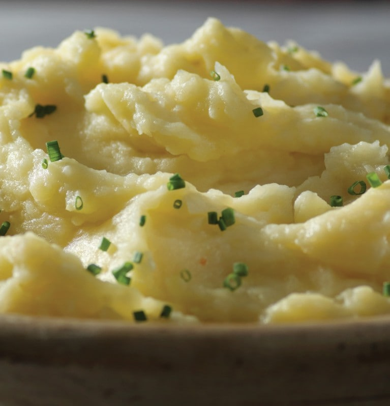 Creamy mashed potato in cast iron skillet sprinkled with green garnish