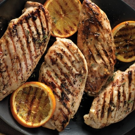 Grilled chicken breasts with grilled orange garnish on a black plate