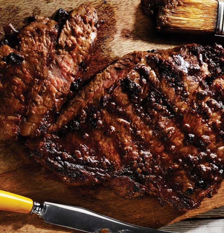 Perfectly seasoned grilled steak sliced on a cutting board with knife