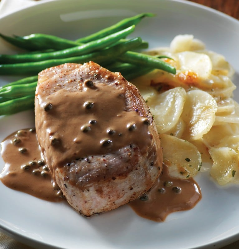 Pork chop smothered in balsamic and cracked pepper sauce served with green beans and scalloped potatoes