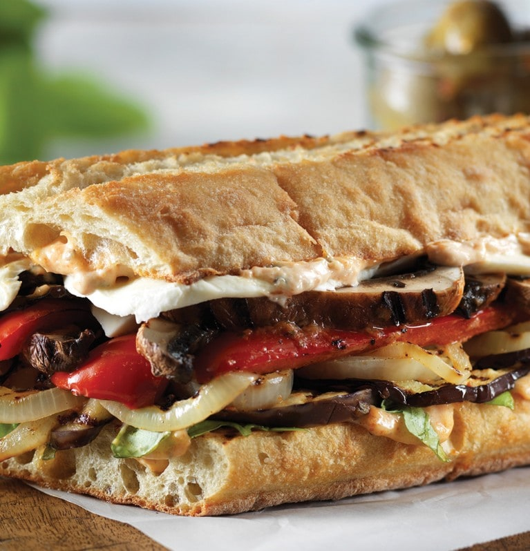 Bagette sandwich with layers of grilled vegetables and cheese