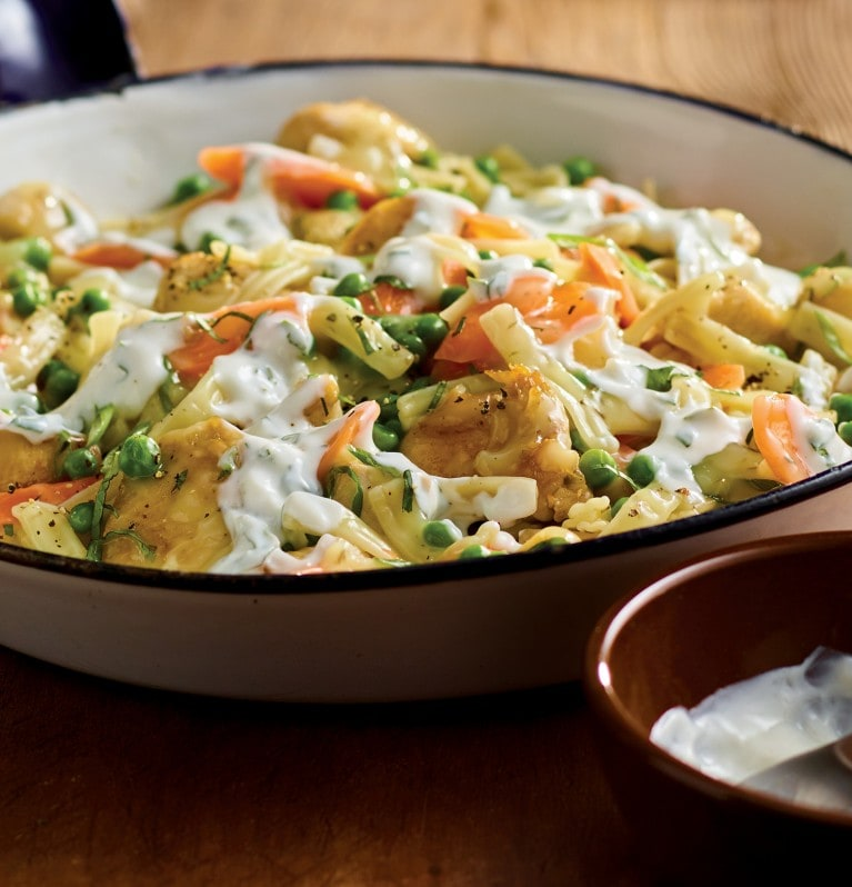 Hands serving butter and herb pasta side dish with chopped mint, peas, sliced carrots and chicken from cast iron pan