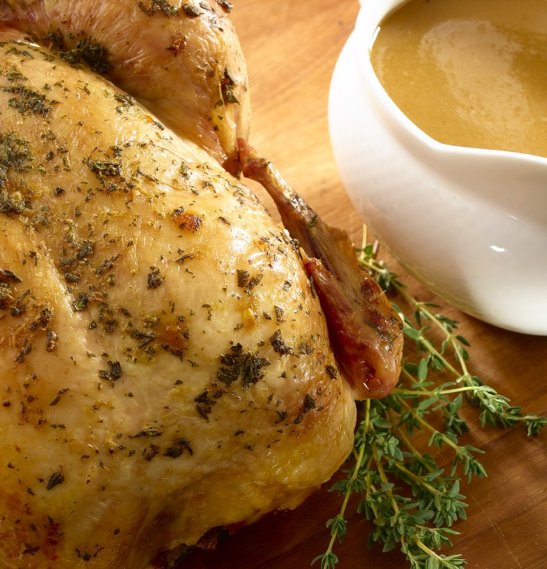 Herb-roasted whole chicken with a full gravy boat