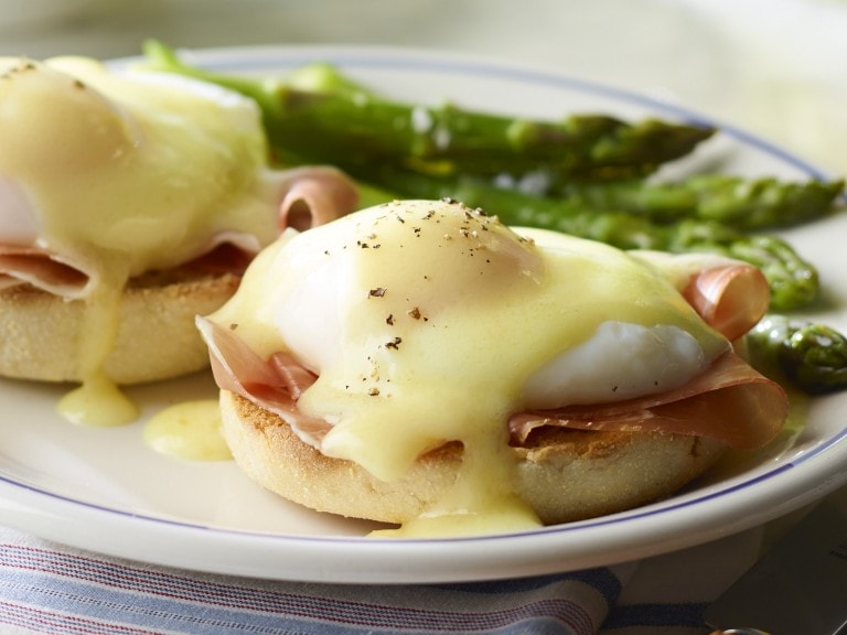 Two eggs benedict served with asparagus and orange juice