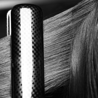 A section of long dark, damaged hair being styled with heat tongs.