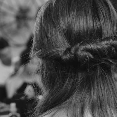 Black and white backstage close up of the back of a model's head, with her long dark hair in a loose braid, with someone straightening a section of her hair with irons