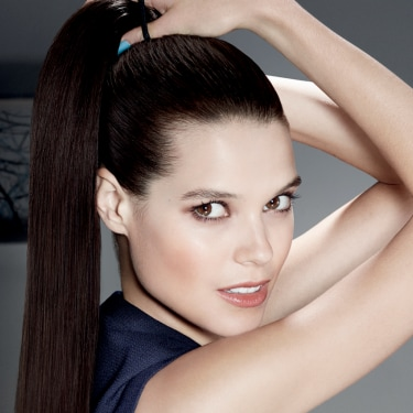 A woman tying her hair into a high pony tail while looking directly into the camera.