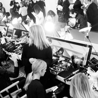 Black and white shot of a busy backstage area featuring models sitting in front of mirrors with hairstylists, photographers and styling tools and hair products