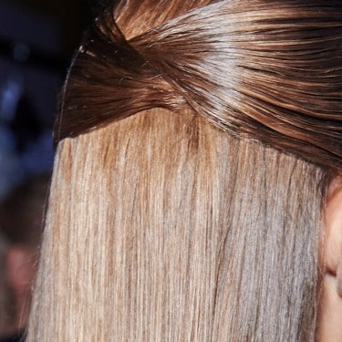 The back of a female model's head. Her long brown hair is gathered into a large chic bow.