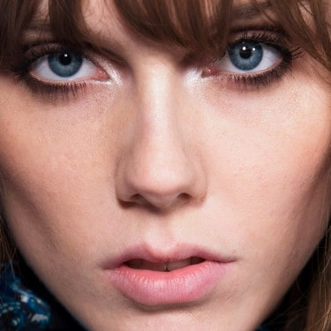 A model staring intensely at the camera with eyebrow length brown bangs