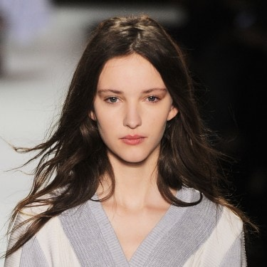 Close up of the head and shoulders of a model on the runway, with long, slightly wavy dark brown hair, wearing a grey and white V-neck sweater or dress