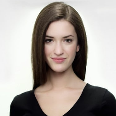 A smiling model with long brown hair in a parting, wearing a black V-neck top